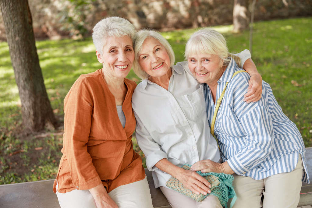 Joyful old women sitting on bench in the park